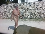 Nudist saggy mature passing by, letting nice tits swing