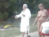 Mature nudist couple with nice saggy tits walks by